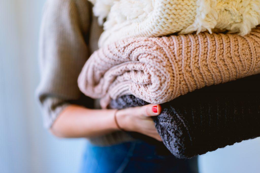 Imagem de uma mulher carregando agasalhos de lã.