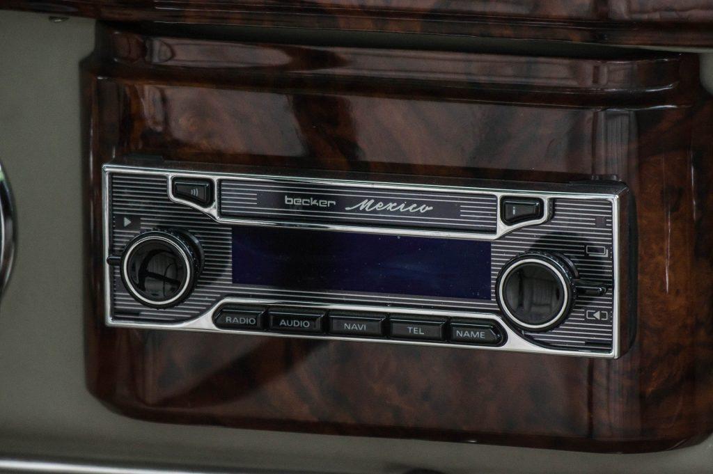 Imagem mostra o close de um rádio automotivo antigo, instalado num painel de acrílico.