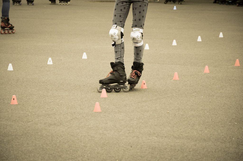 Imagem mostra as pernas de uma patinadora no momento em que passa por obstáculos de treino, com o chassi do patins direto à mostra.