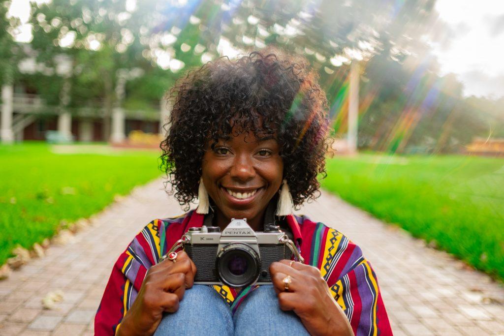 Imagem mostra um mulher sorrindo para a câmera, enquanto segura uma outra câmera fotográfica com as duas mãos, na altura do peito.