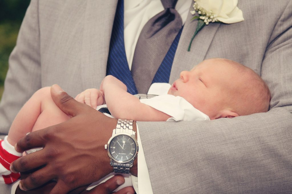 Imagem mostra um bebê recém-nascido nos braços de um homem com terno e flor na lapela do paletó.