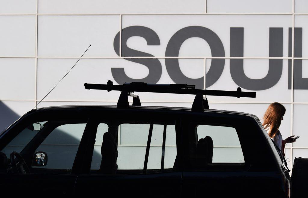 Imagem mostra o teto de um carro com um suporte compacto instalado. Ao fundo, uma mulher mexe no seu celular.