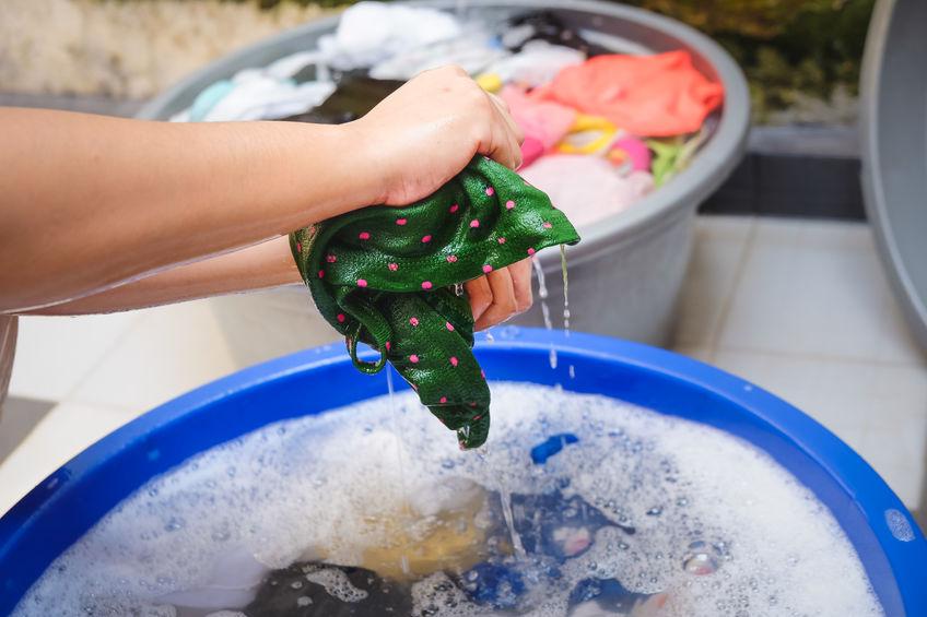 Mulher lavando roupa no balde.