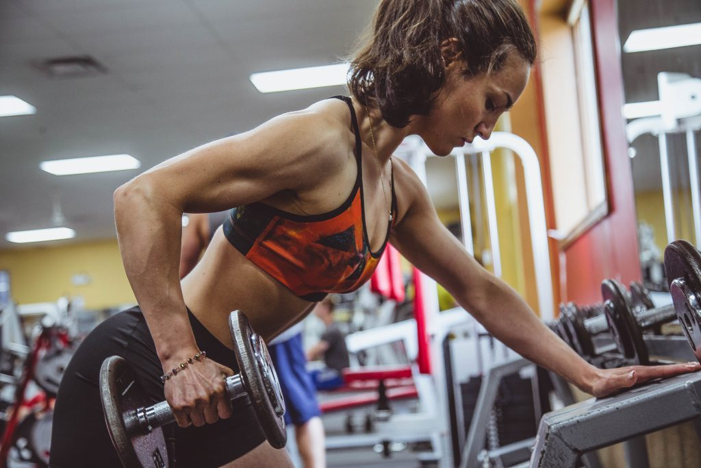 Mulher puxando peso na academia de ginástica.