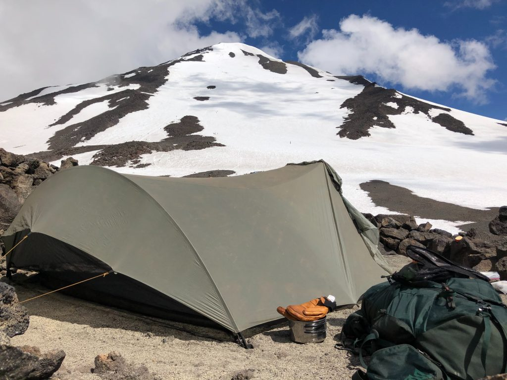 Imagem mostra uma barraca extensa, montada ao lado de um cume de montanha, com malas e objetos de acampamento ao seu redor.