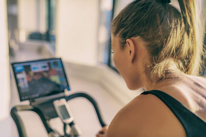 Imagem mostra uma mulher, de costas para a câmera, usando uma bicicleta ergométrica, cujo painel, em segundo plano, é visível, mas desfocado.