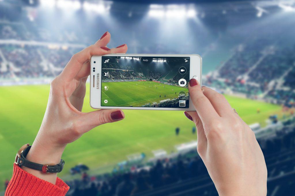 Mulher tirando foto com celular Samsung.