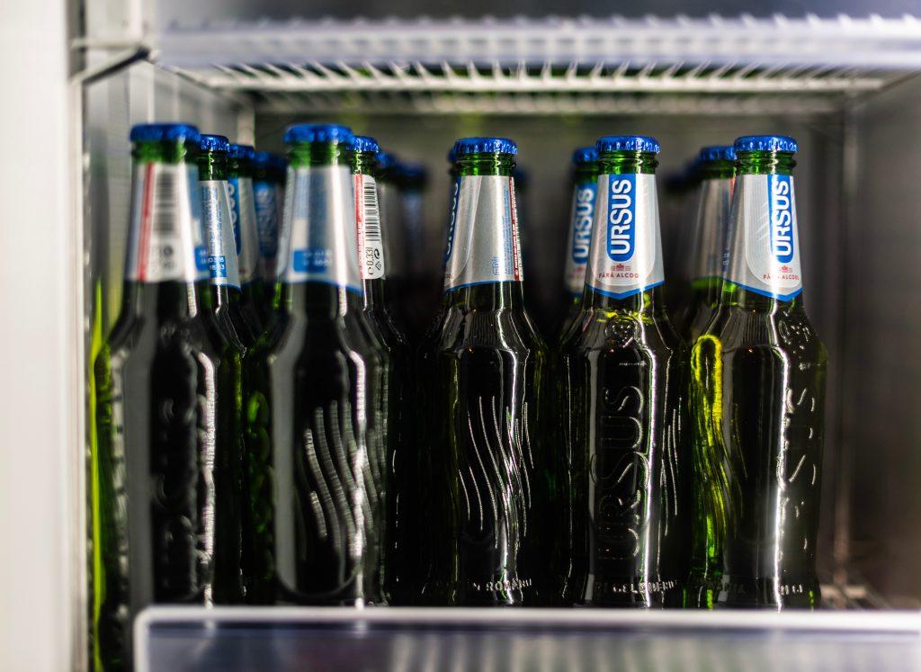 Imagem mostra uma série de garrafas de cerveja, acomodadas na vertical, em cima de uma prateleira de uma cervejeira.