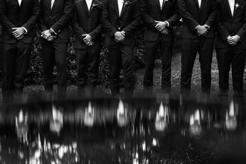 Imagem em preto e branco mostra uma fileira de homens, cujos rostos não são mostrados no quadro, enfileirados lado a lado. Todos estão de terno e juntam as mãos em frente à cintura.