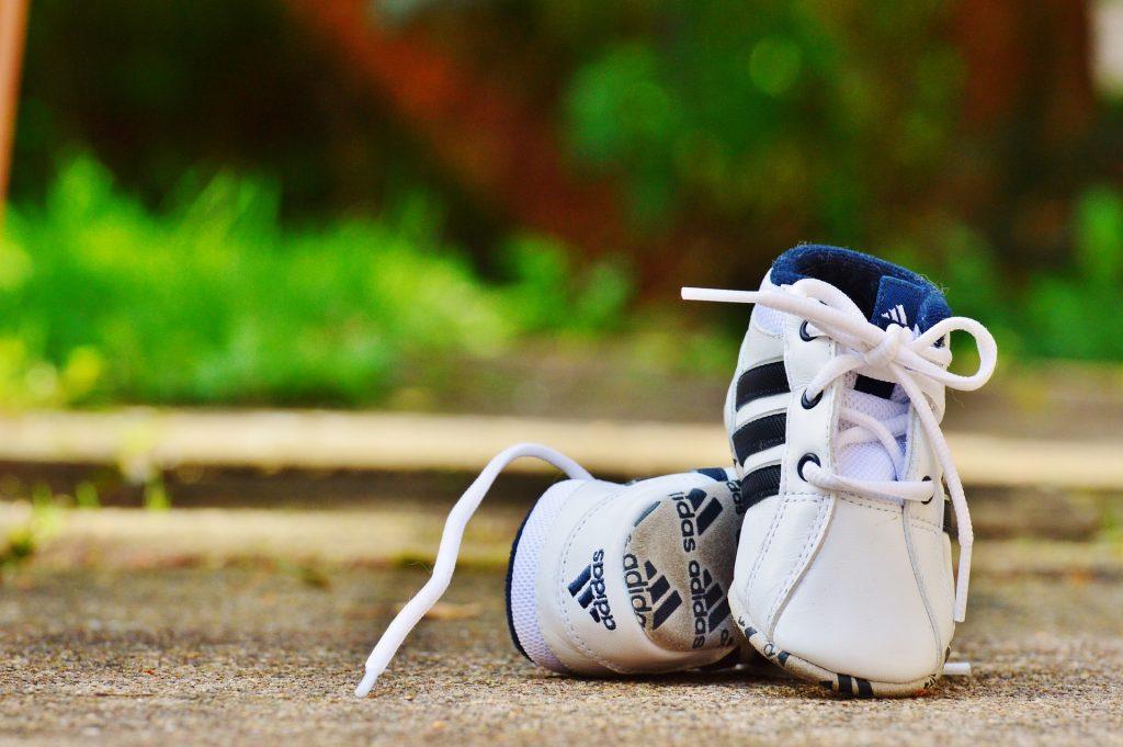 Imagem mostra um par de chuteiras infantis da Adidas apoiadas no concreto, com foco seletivo.