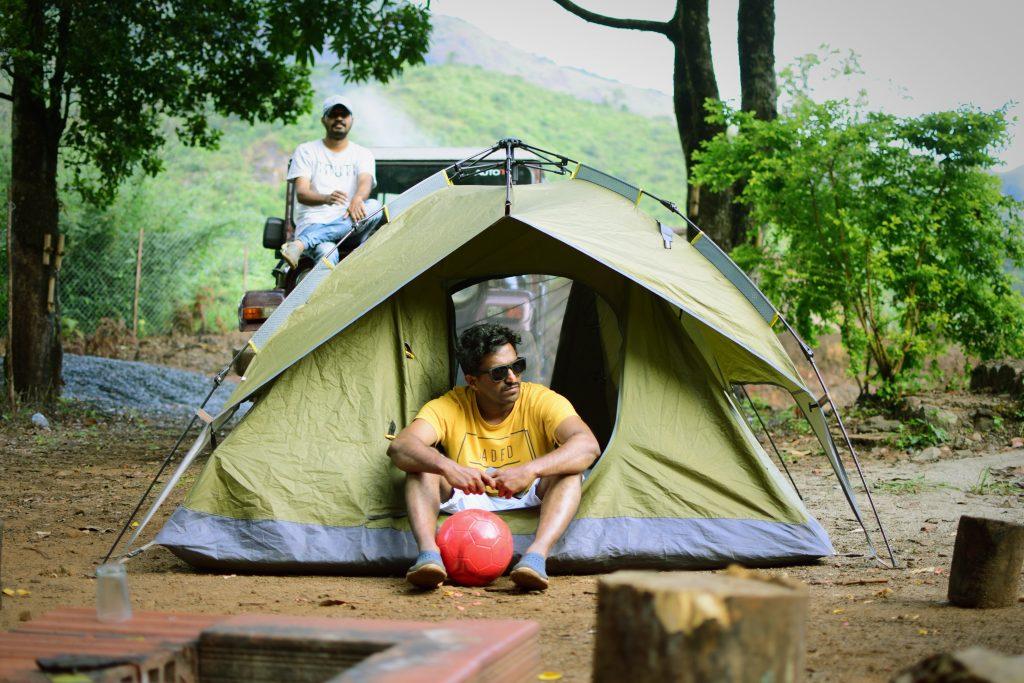 Imagem mostra um homem sentado dentro de uma barraca montada sobre um chão de terra batida. Há outro homem ao fundo, sentado no capô de um jipe.