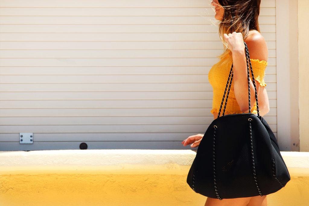 Imagem de uma mulher carregando uma bolsa grande.