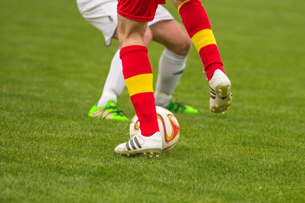 Imagem mostra um jogador, representado no quadro somente por suas pernas, e usando chuteiras Adidas, no momento que parte para driblar o adversário à sua frente, também representado por suas pernas.