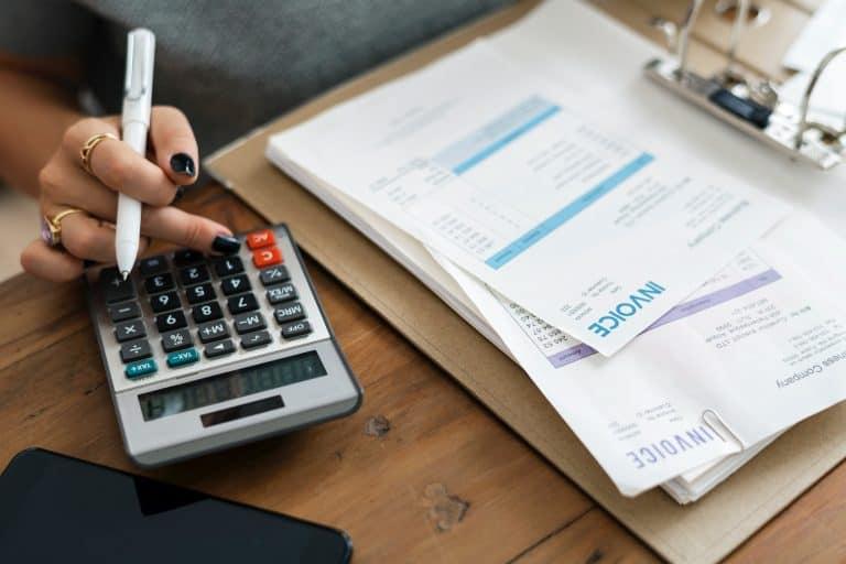 Mulher usando calculadora com prancheta.