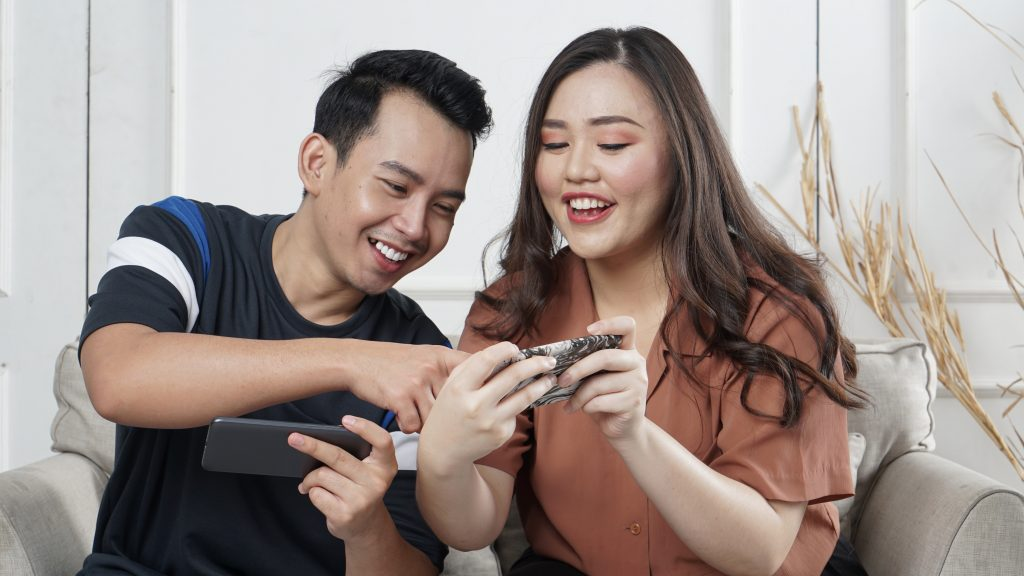 Imagem de um casal jogando pelo celular.