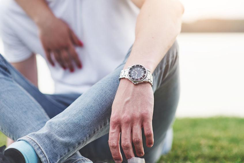 Imagem de um homem usando um relógio com pulseira de aço.