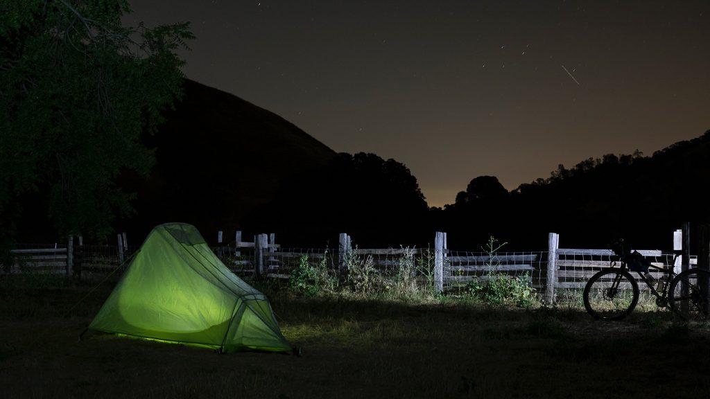 Imagem mostra uma pequena barraca montada sobre um pasto e iluminada por dentro, em frente à uma cerca de madeira.