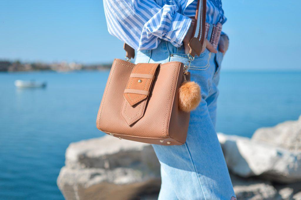 Imagem de uma mulher usando uma bolsa de couro.