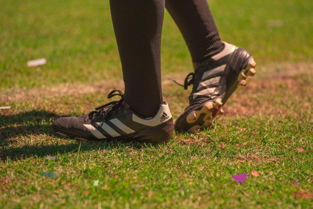 Imagem um par de chuteiras pretas da Adidas, calçadas por uma perna com meião preto. O pé esquerdo pisa na grama, enquanto o direito somente apoia o bico no gramado.