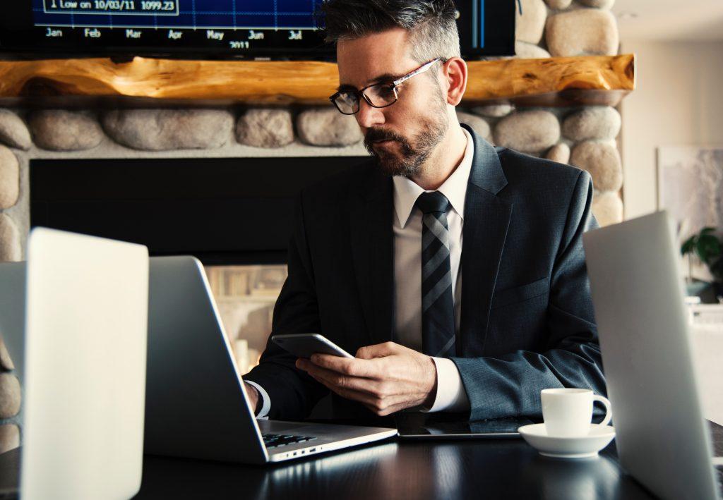 Homem de terno e gravata checando celular e notebook.