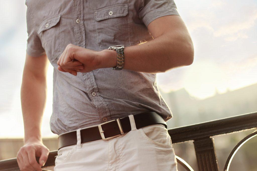 Imagem de um homem consultando as horas em um relógio.