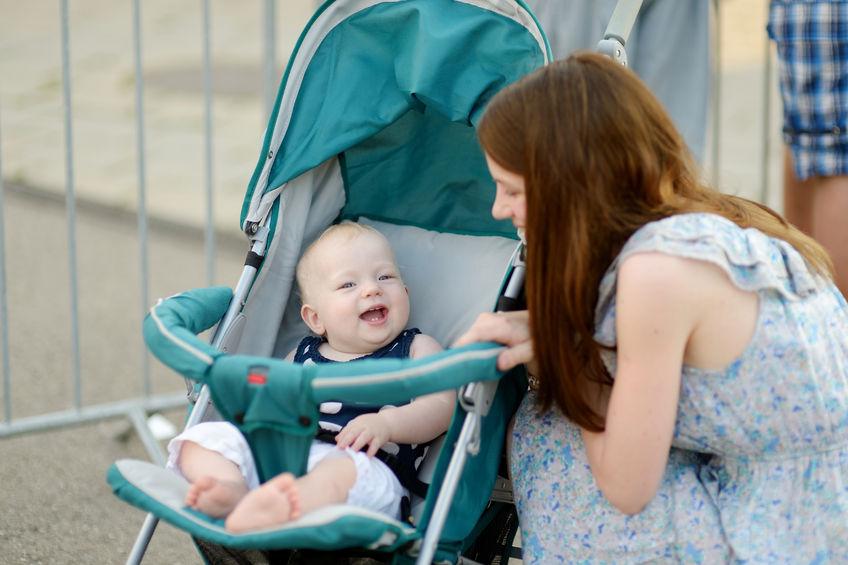Mulher agachada conversando com bebê em carrinho.