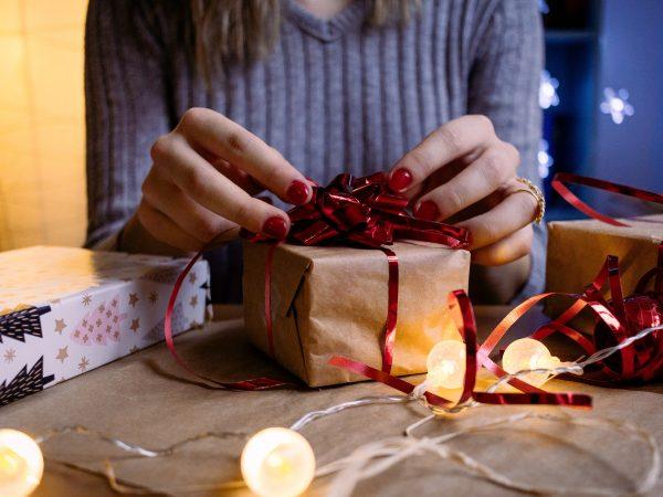 Imagem mostra uma mão feminina abrindo o embrulho de uma caixa de presente.