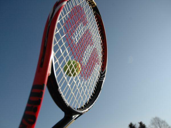 """Imagem mostra o close da rede de uma raquete Wilson, com seu tradicional """"W"""" desenhado, quando uma bola está prestes a ser rebatida."""