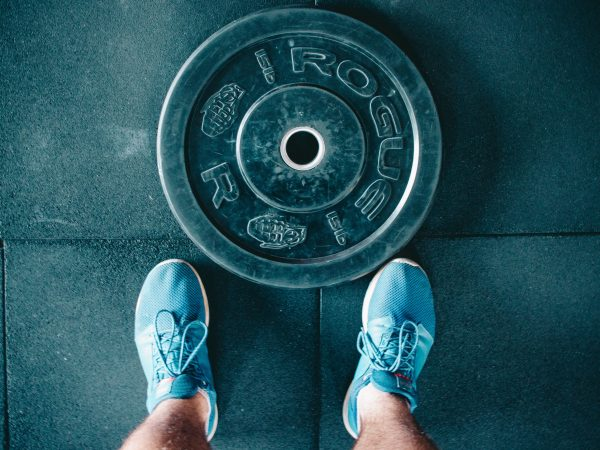 Imagem mostra, do alto, uma grande anilha comum no chão, com dois pés à sua frente.