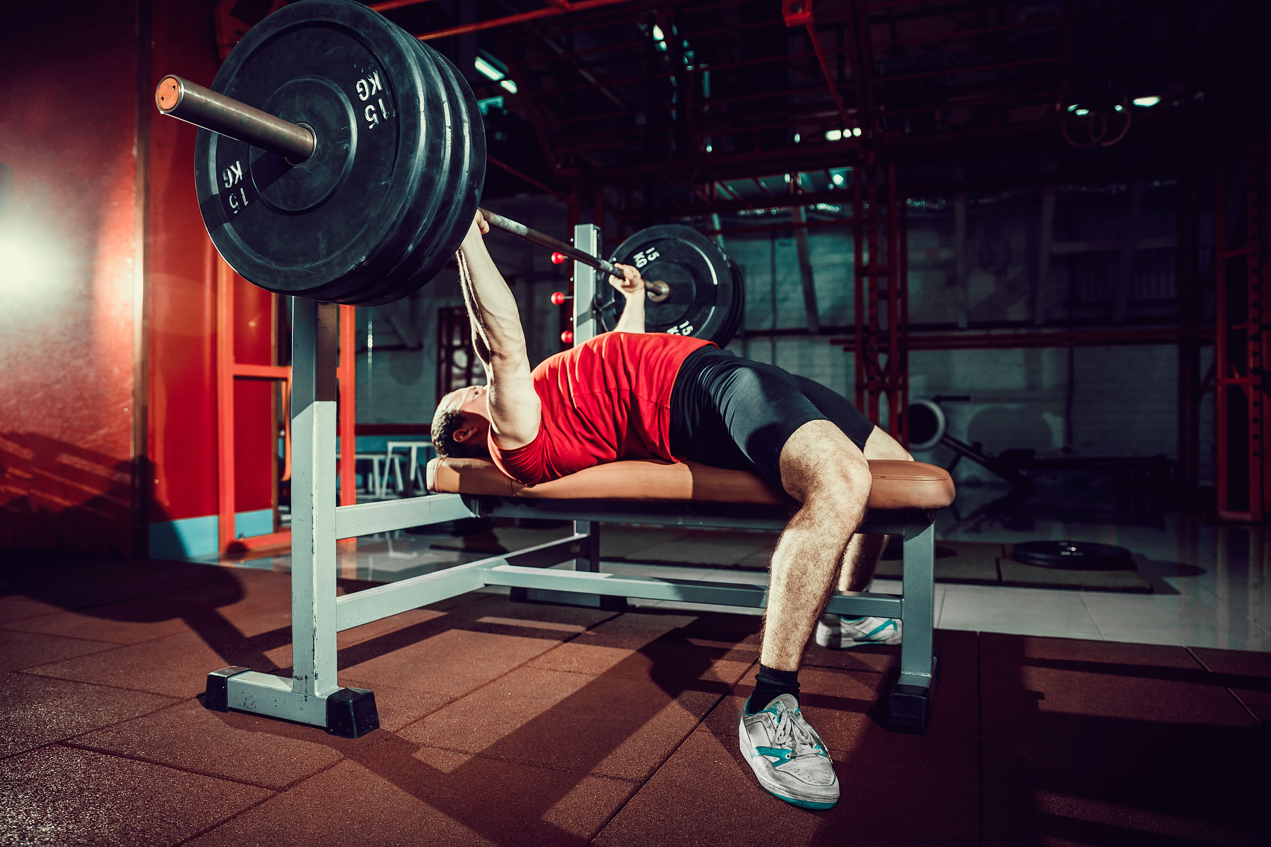 Imagem mostra um homem deitado num banco supino, levantando uma barra com anilhas de 15 quilos .