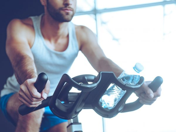 Imagem mostra um homem pedalando numa bicicleta ergométrica, com foco nas suas mãos, que seguram as alças do do painel.