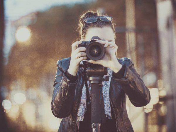 Mulher fotografando com câmera Canon.
