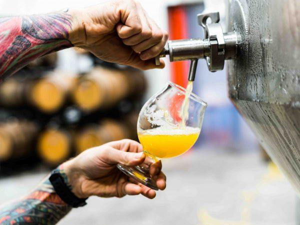 Imagem mostra uma pessoa, retratada apenas pelas suas mãos, servindo-se de um chopp, com a mão esquerda segurando o copo e a direita operando a torneira da chopeira.
