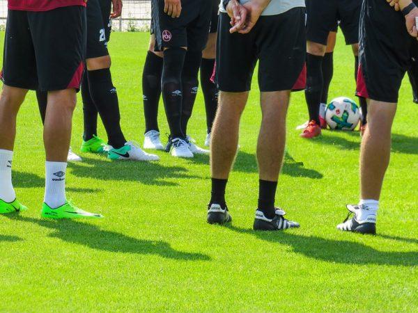 Imagem mostra jogadores reunidos, em círculo, com destaque para as pernas dos atletas calçando chuteiras de diversas marcas, cores e modelos.