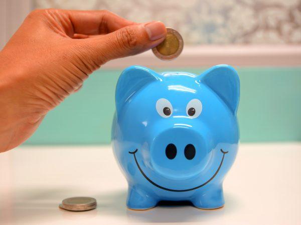 Uma pessoa está prestes a pôr uma moeda dentro de um cofrinho azul em forma de porco.