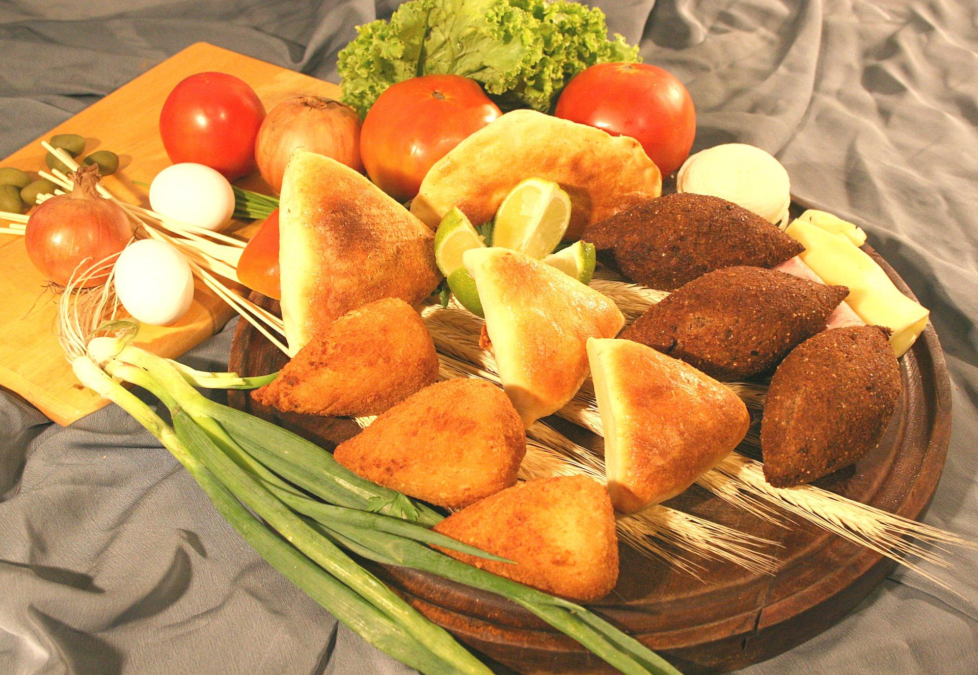 Prato de madeira com coxinhas, esfihas e quibes. Ao lado, há tomates, alho poró, alface e ovos espalhados.