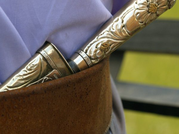 Na foto está uma faca em metal trabalhada com estampas no cinto de uma pessoa.