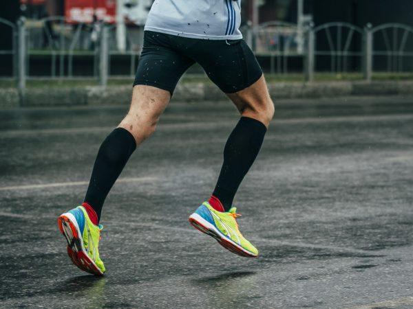 Imagem mostra um par de pernas com meião de uma pessoa deitada na grama. Ele tem chuteiras calçadas nos dois pés e um pequeno cone de treino ao seu lado.