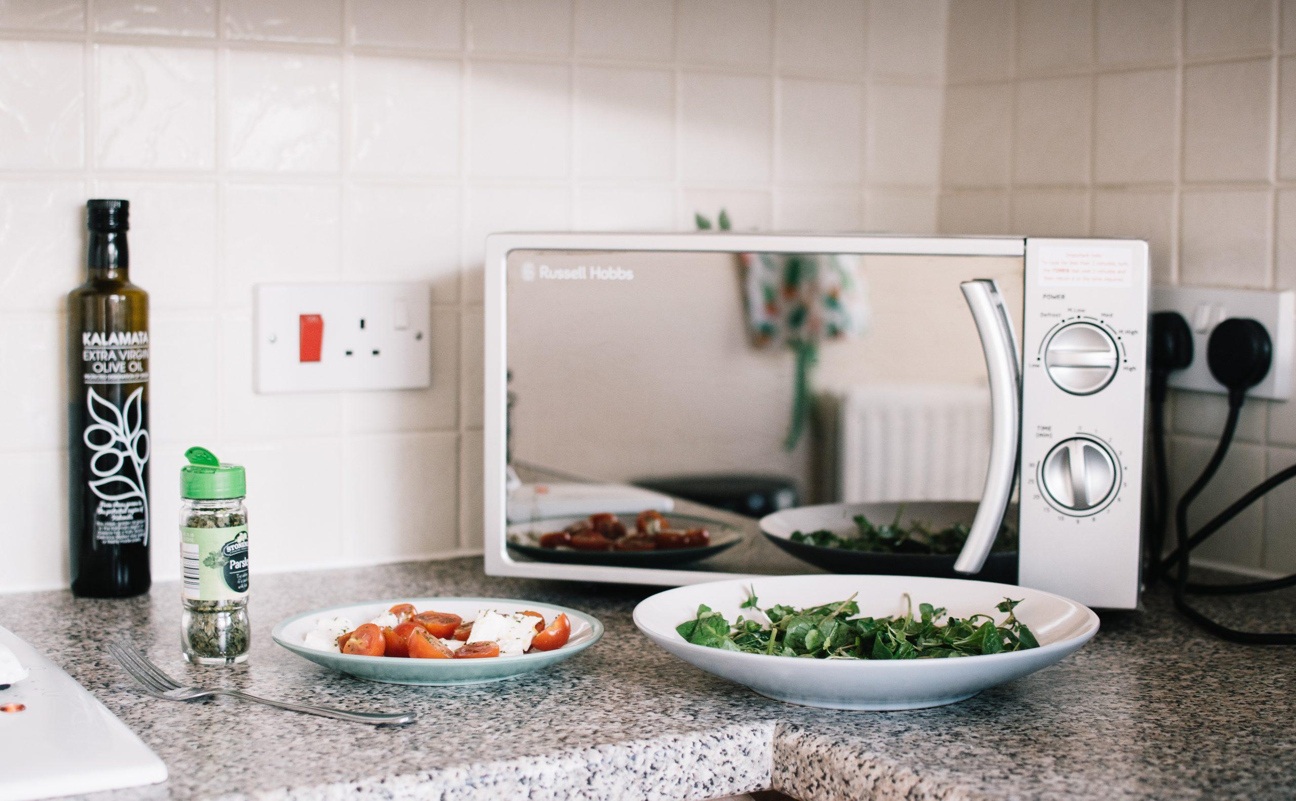 Micro-ondas apoiado em bancado com pratos à frente aguardando para serem aquecidos