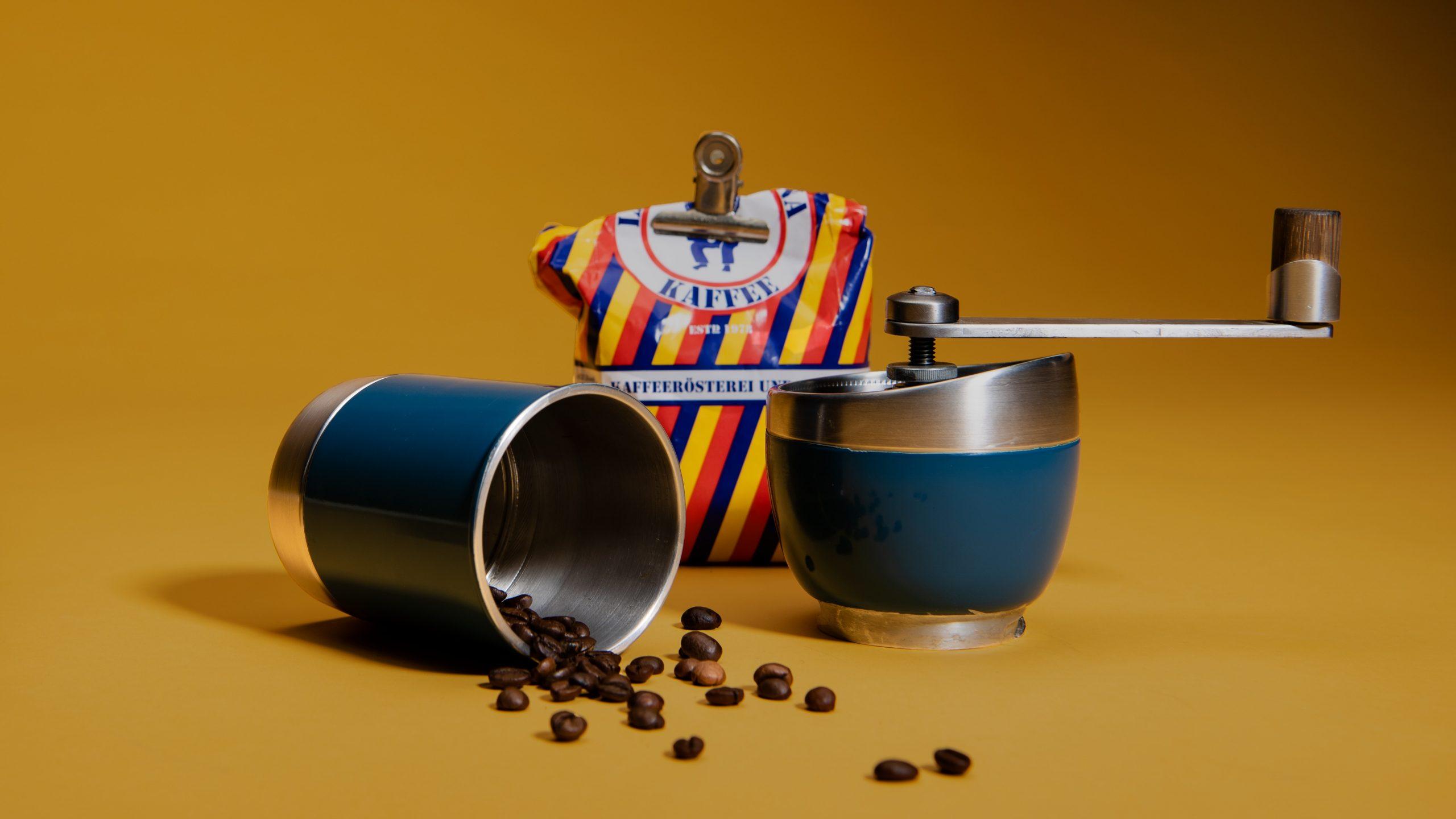 Imagem de moedor de café manual com grãos espalhados