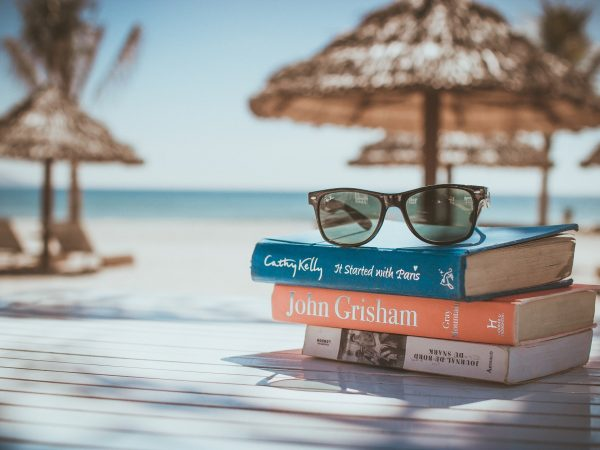 Óculos de sol polarizado em cima da mesa com livros.