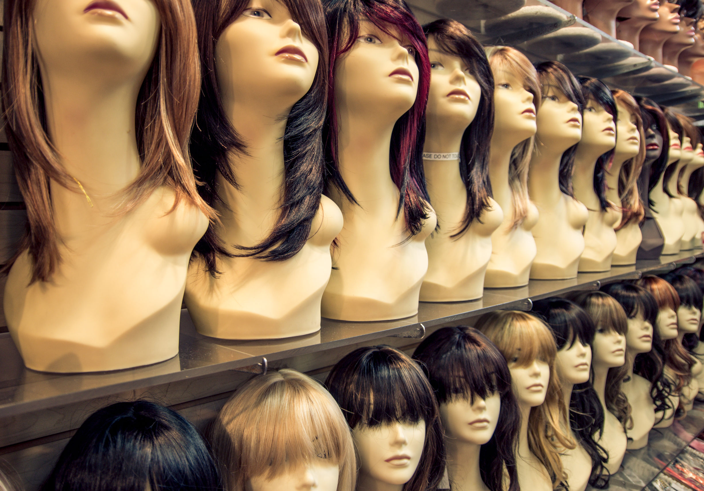 Foto de diversas perucas em cabeças de manequins enfileiradas, cada um delas de uma cor e estilo.