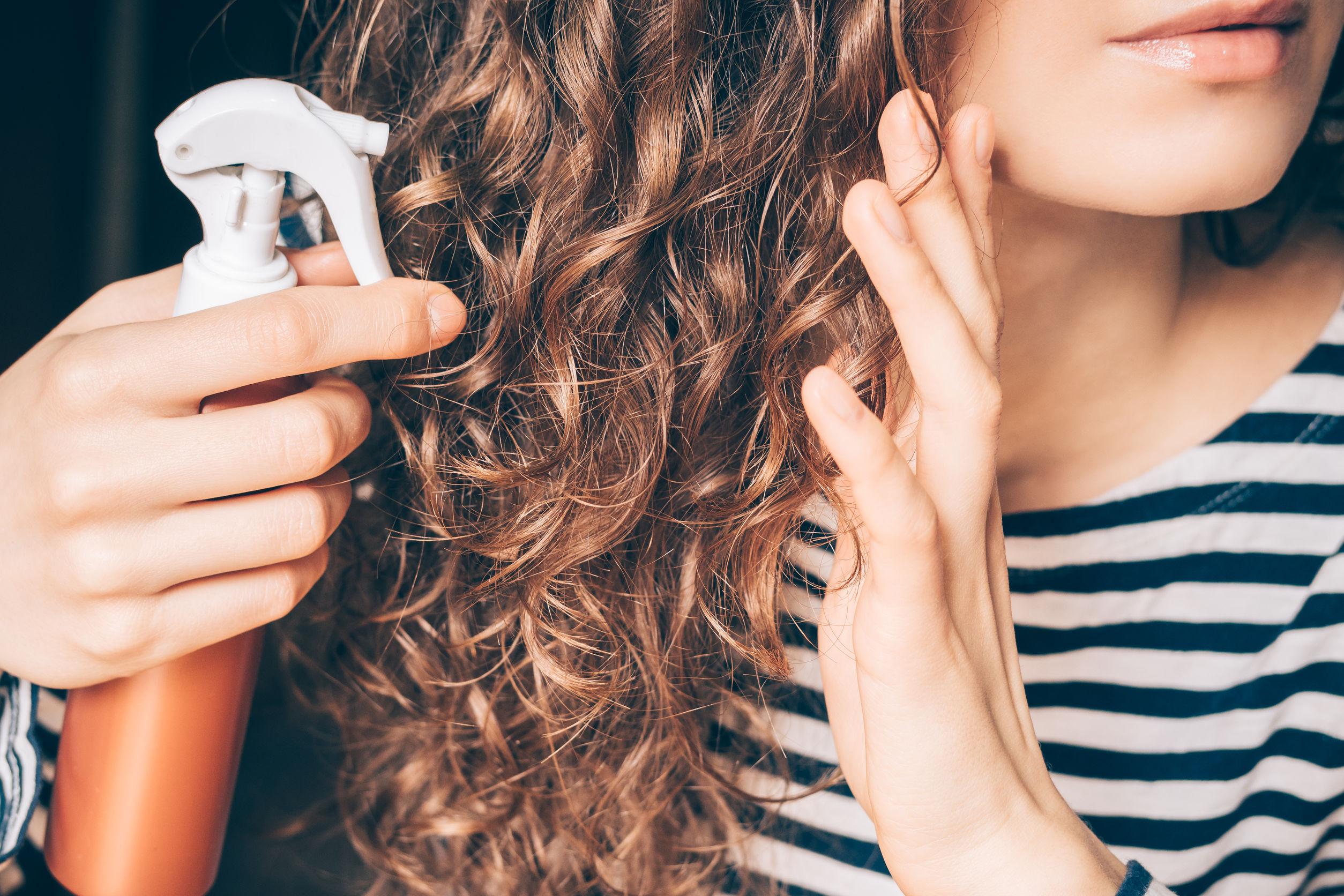 Imagem de uma mulher aplicando queratina líquida no cabelo.