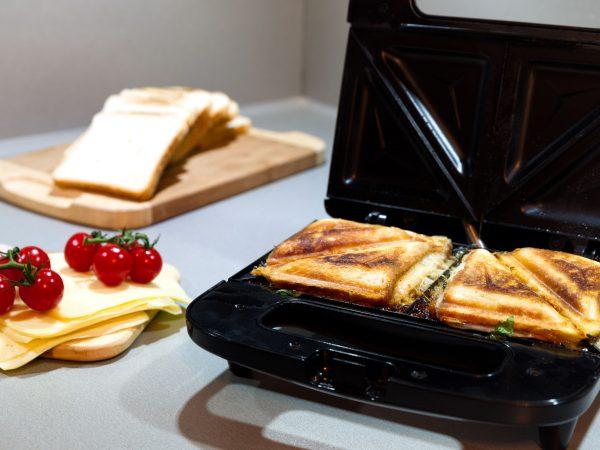 Sanduicheira com dois mistos quentes ao lado de tábua com ingredientes