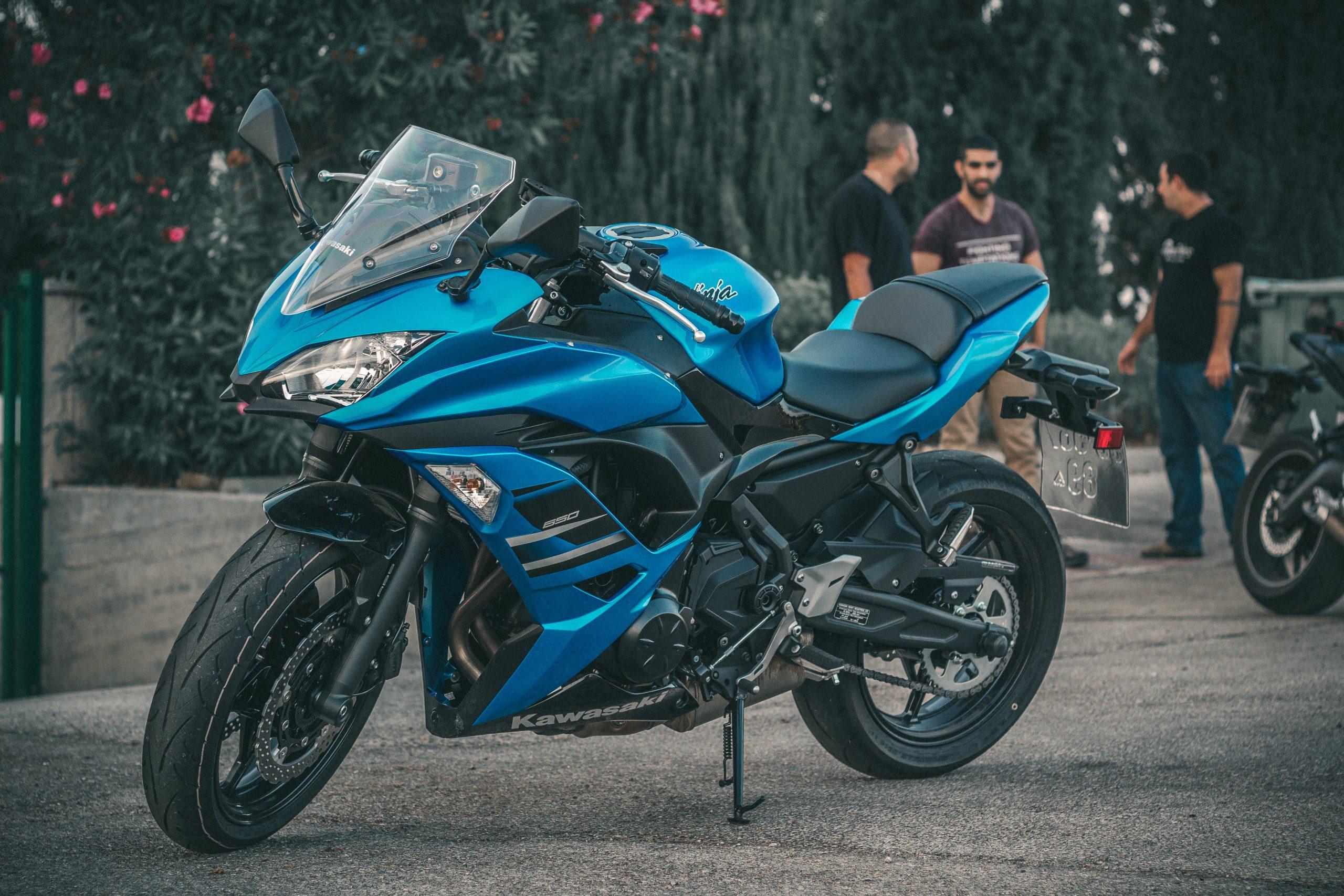 Moto azul com pessoas ao fundo.