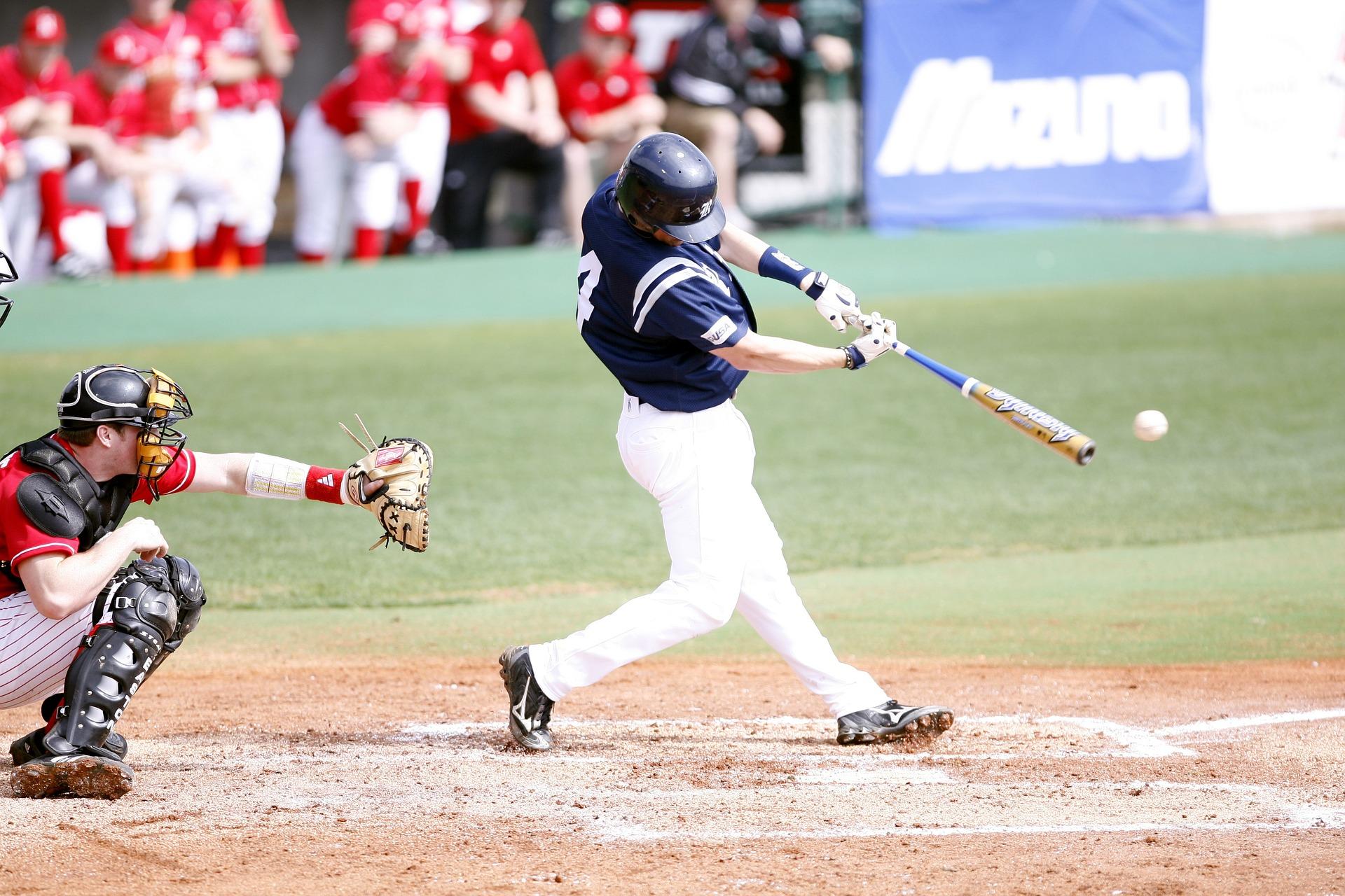 Um apanhador agachado e um rebatedor de pé rebatendo uma bola com um taco de beisebol