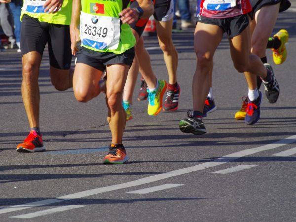 Imagem mostra ou pares de tênis de corrida de seis corredores em meio à uma maratona de rua.