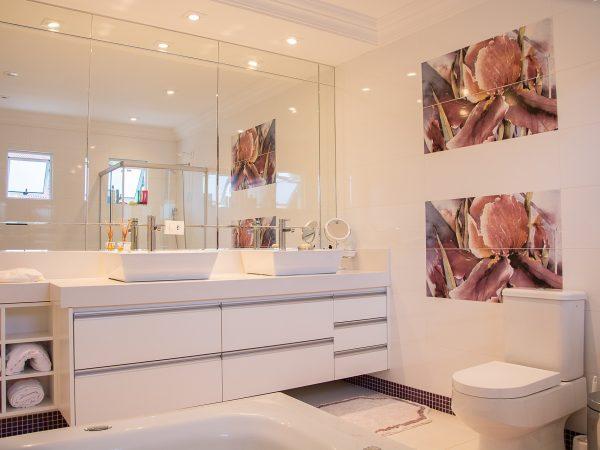 Um banheiro com um vaso sanitário, alguns azulejos decorados, uma pia grande, gavetas, porta-toalhas, tapete e um espelho enorme