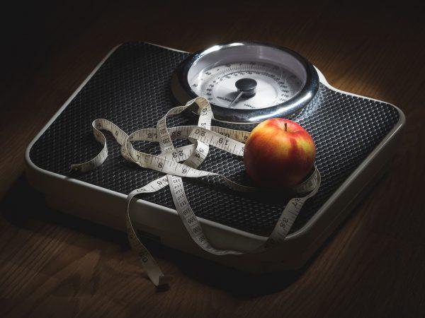Imagem de balança com fita métrica e maçã em destaque