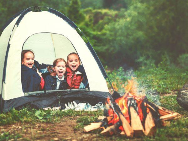 Imagem mostra três crianças dentro de uma barraca montada num descampado. Elas estão rindo na entrada da barraca, com uma fogueira branda em frente a elas.